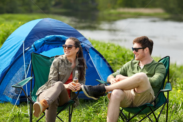 happy couple drinking beer at campsite tent Stock photo © dolgachov