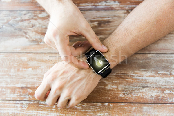 close up of hands with light bulb on smart watch Stock photo © dolgachov
