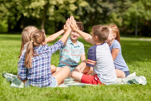 Groupe heureux enfants high five extérieur Photo stock © dolgachov