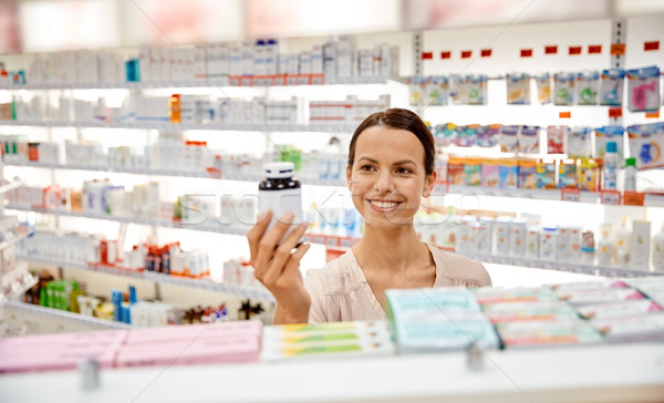happy female customer with drug jar at pharmacy Stock photo © dolgachov