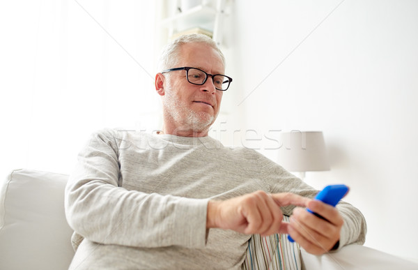 happy senior man texting on smartphone at home Stock photo © dolgachov