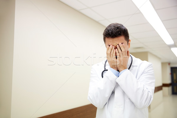 sad or crying male doctor at hospital corridor Stock photo © dolgachov