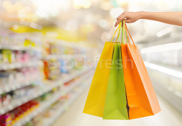 hand with shopping bags over supermarket Stock photo © dolgachov