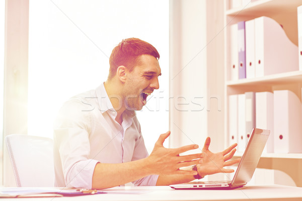 angry businessman with laptop and papers in office Stock photo © dolgachov