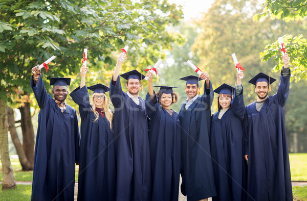 Stock photo: happy students in mortar boards with diplomas