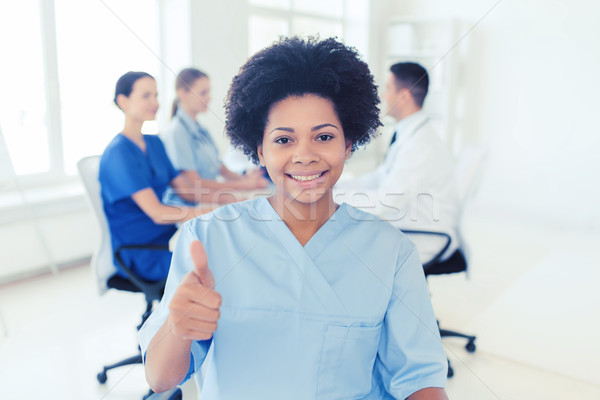 happy female doctor or nurse showing thumbs up Stock photo © dolgachov