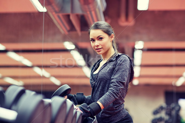 Stock photo: young woman choosing dumbbells in gym