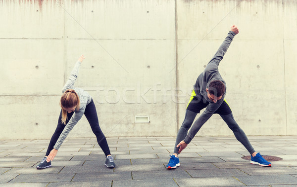 close up of couple stretching on city street Stock photo © dolgachov