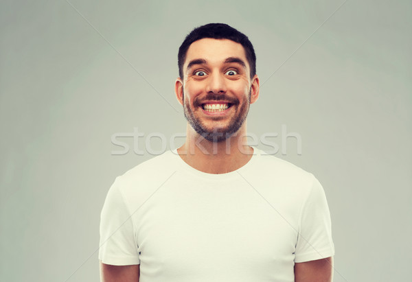 man with funny face over gray background Stock photo © dolgachov