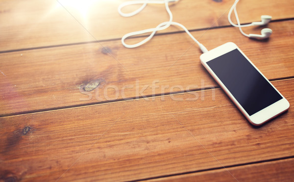 close up of blank smartphone and earphones on wood Stock photo © dolgachov