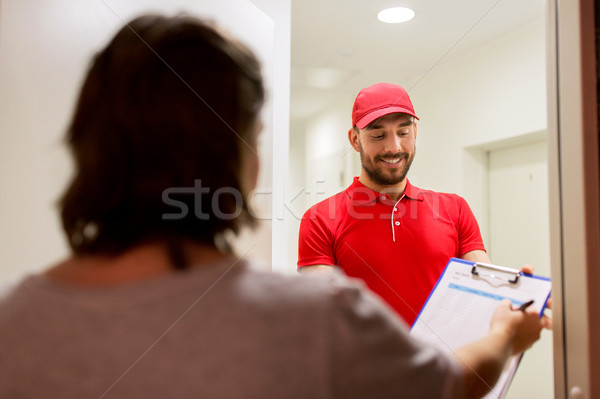 deliveryman with clipboard at customer home Stock photo © dolgachov