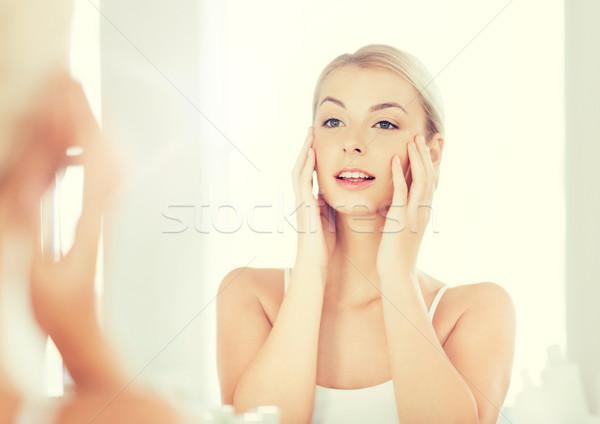 happy young woman looking to mirror at bathroom Stock photo © dolgachov