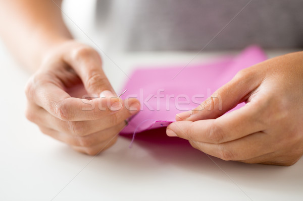 woman with needle stitching fabric pieces Stock photo © dolgachov