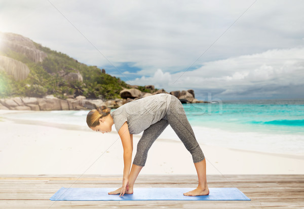 woman making yoga intense stretch pose on beach Stock photo © dolgachov