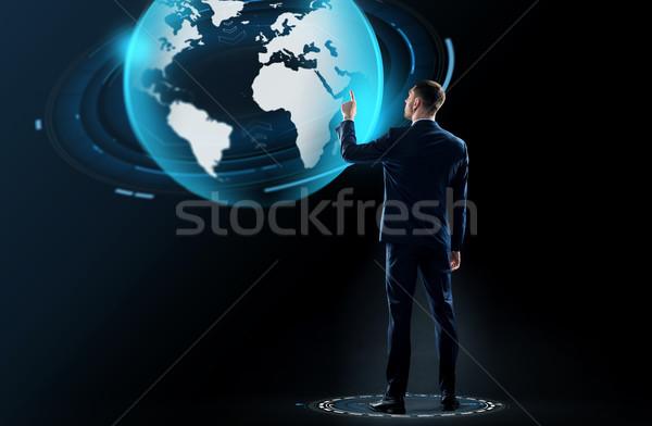 üzletember öltöny megérint Föld földgömb hologram Stock fotó © dolgachov