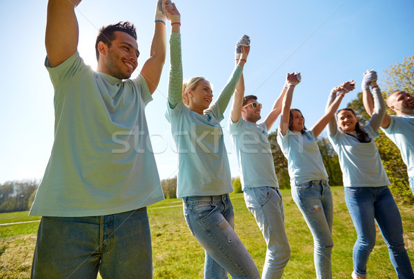 group of happy volunteers holding hands outdoors Stock photo © dolgachov