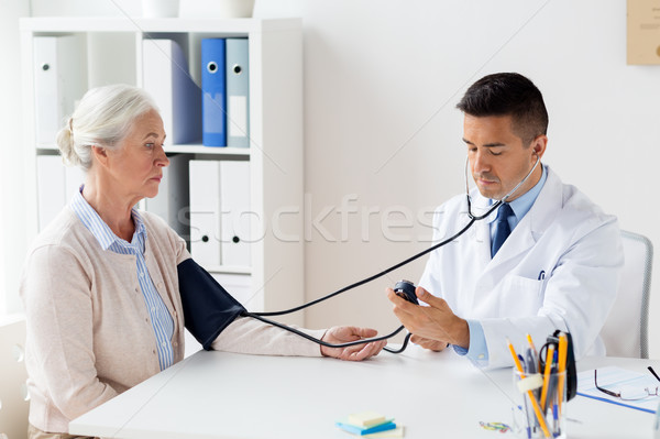 senior woman and doctor with tonometer at hospital Stock photo © dolgachov
