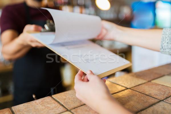 bartender showing menu to customer at bar Stock photo © dolgachov
