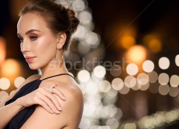 woman wearing jewelry over christmas lights Stock photo © dolgachov