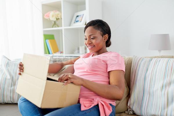 happy pregnant woman opening parcel box at home Stock photo © dolgachov