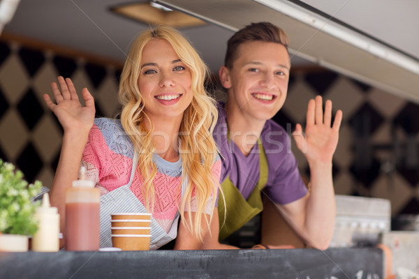 Stock photo: happy young sellers waving hands at food truck