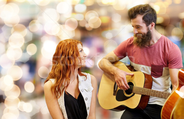 couple of musicians playing guitar over lights Stock photo © dolgachov