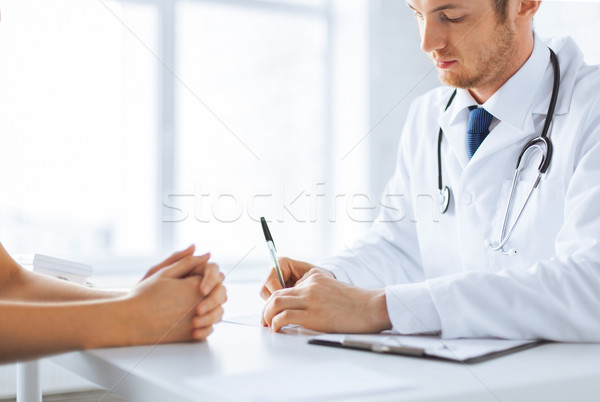 Stock photo: patient and doctor taking notes