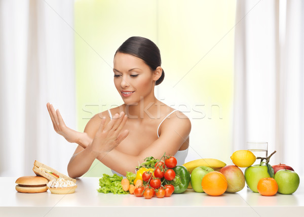 woman with fruits rejecting junk food Stock photo © dolgachov