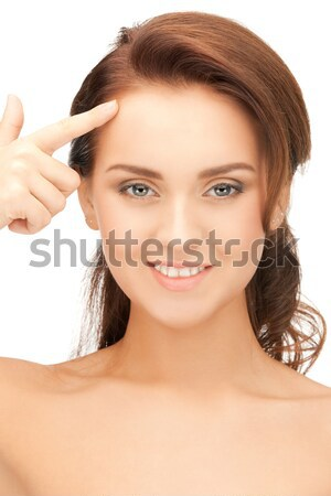 young calm woman pointing to her forehead Stock photo © dolgachov