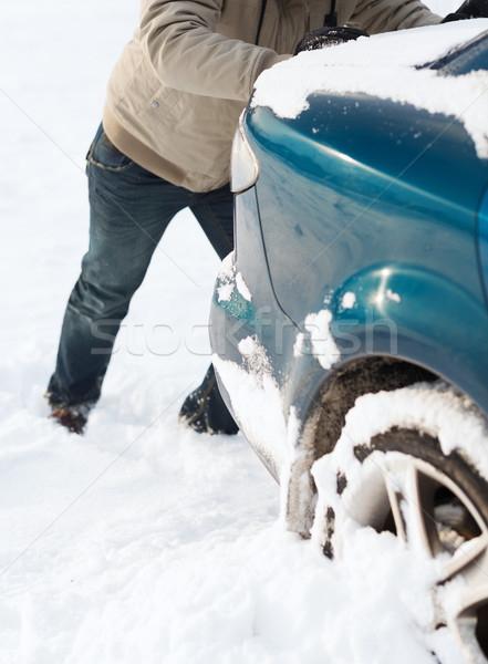Stock photo: closeup of man pushing car stuck in snow