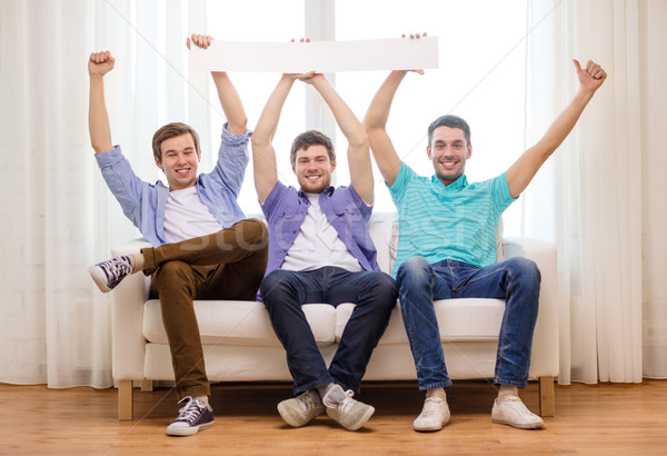 smiling male friends holding white blank banner Stock photo © dolgachov