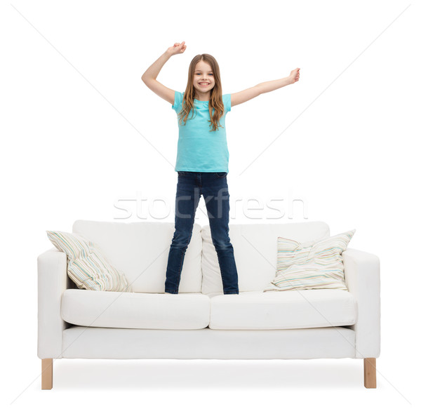 smiling little girl jumping or dancing on sofa Stock photo © dolgachov