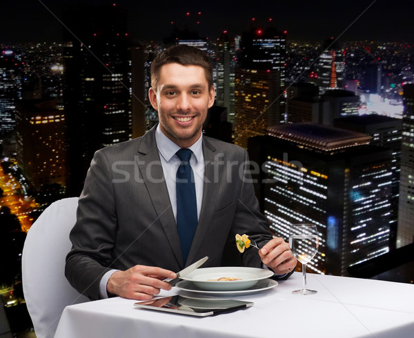 Souriant homme manger plat principal restaurant Photo stock © dolgachov