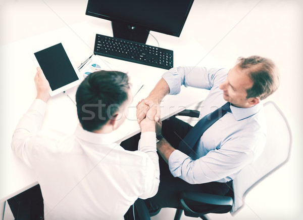 Stock photo: businessmen shaking hands in office