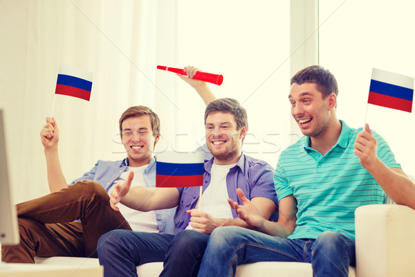 happy male friends with flags and vuvuzela Stock photo © dolgachov