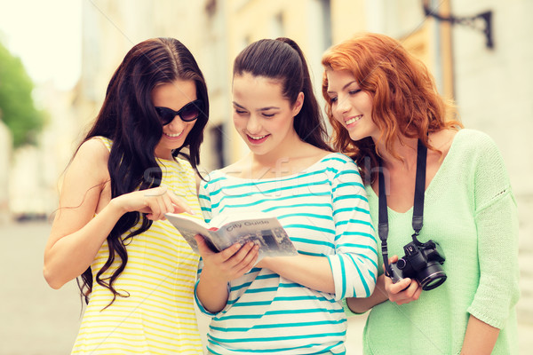 smiling teenage girls with city guide and camera Stock photo © dolgachov