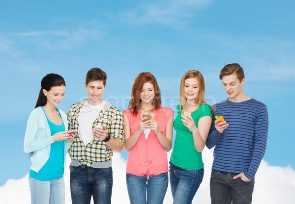 Sonriendo estudiantes smartphones educación moderna tecnología Foto stock © dolgachov