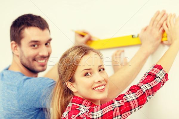 couple building using spirit level to measure Stock photo © dolgachov