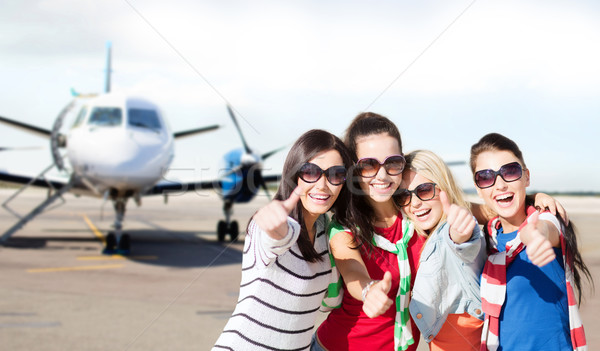 happy teenage girls showing thumbs up at airport Stock photo © dolgachov