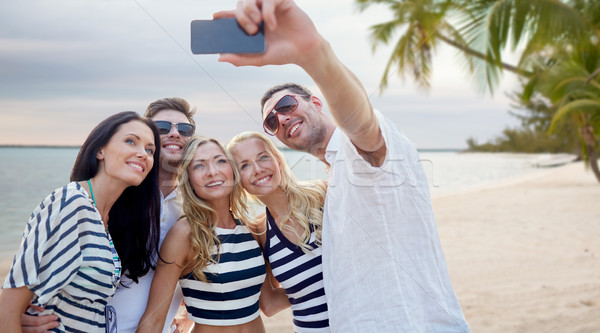 Stock photo: friends on beach taking selfie with smartphone