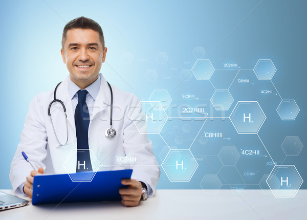 happy doctor with clipboard over blue background Stock photo © dolgachov