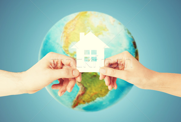 Stock photo: couple hands holding green house over earth globe