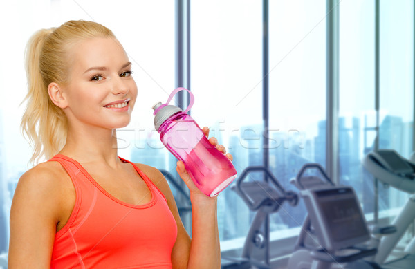 happy woman drinking water from bottle in gym Stock photo © dolgachov