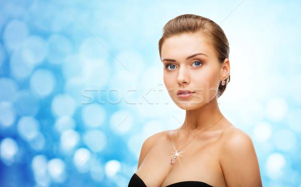 woman wearing shiny diamond earrings and pendant Stock photo © dolgachov