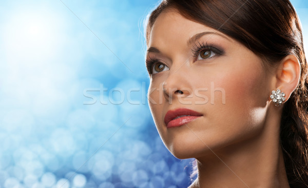 Stock photo: woman with diamond earring over blue lights