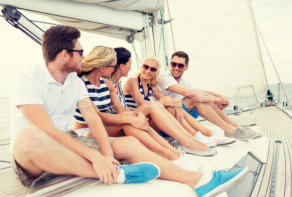 Uśmiechnięty znajomych posiedzenia jacht pokład wakacje Zdjęcia stock © dolgachov