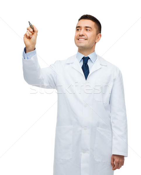 smiling male doctor writing something with marker Stock photo © dolgachov