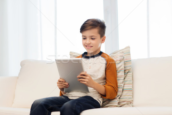 smiling boy with tablet computer at home Stock photo © dolgachov
