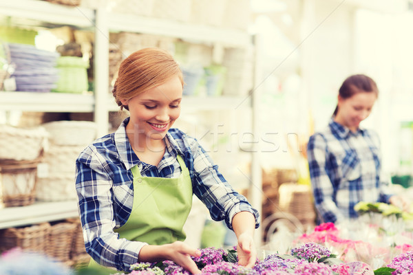 Stock photo: happy woman taking care of flowers in greenhouse