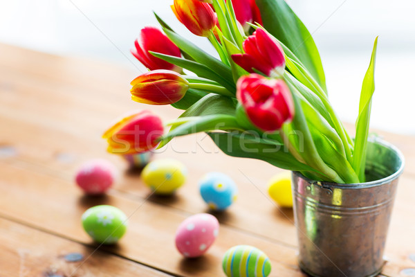 close up of easter eggs and flowers in bucket Stock photo © dolgachov